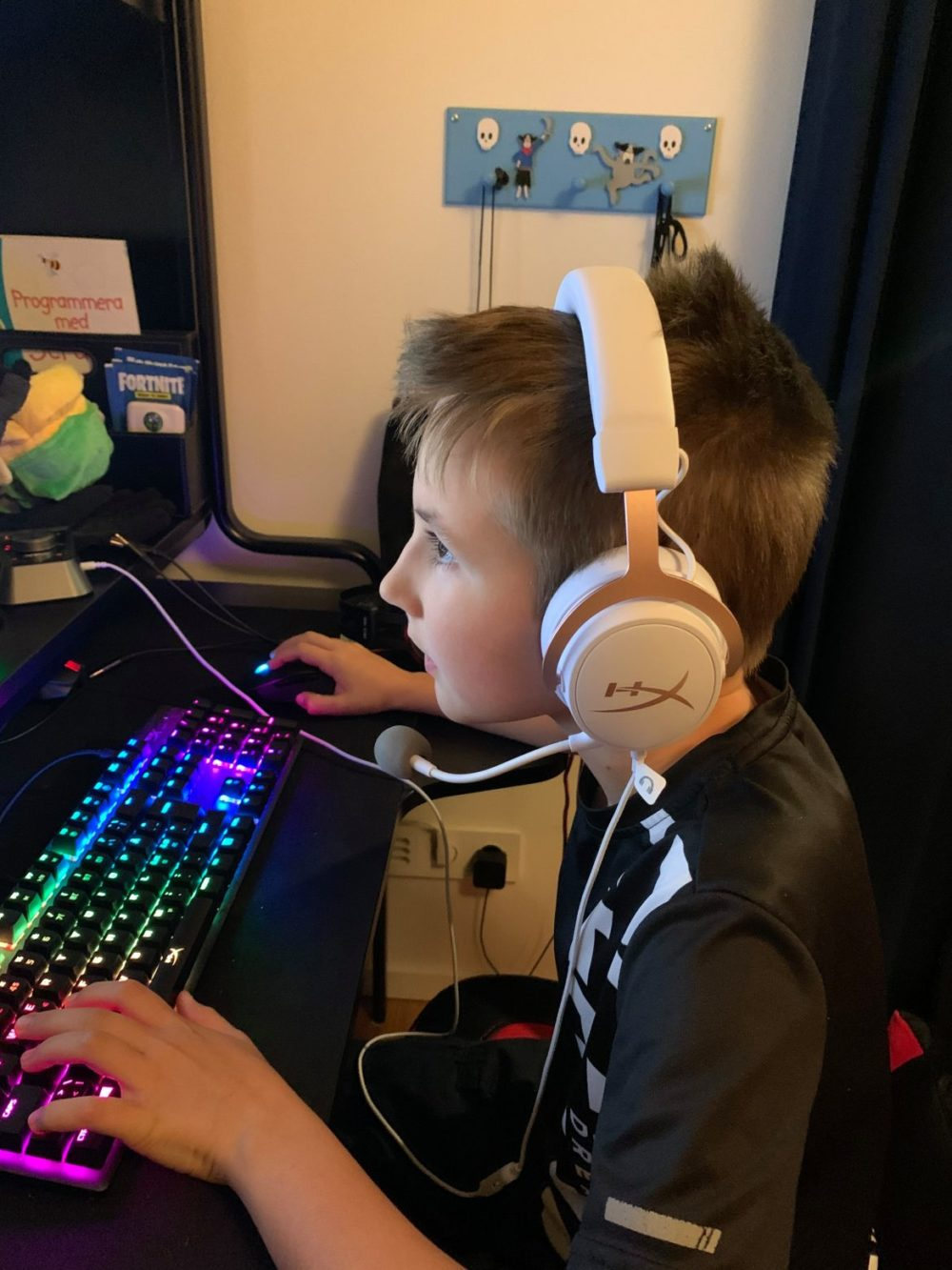 Boy playing PC with HyperX Cloud Mix Rose Gold
